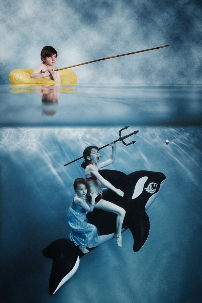 Kids underwater on an orca
